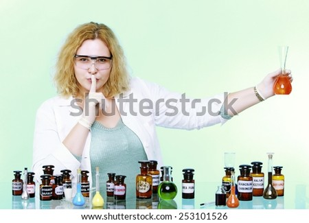 chemist woman or girl student or female laboratory assistant or scientific researcher with chemical glassware test flask, hand silence sign, saying hush be quiet. Isolated on white background - stock photo