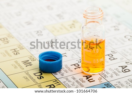 Chemistry: Chromatographic vial filled with orange liquid and a blue plastic cap on the periodic table of elements - stock photo