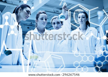 Chemistry students looking at a liquid against science graphic - stock photo