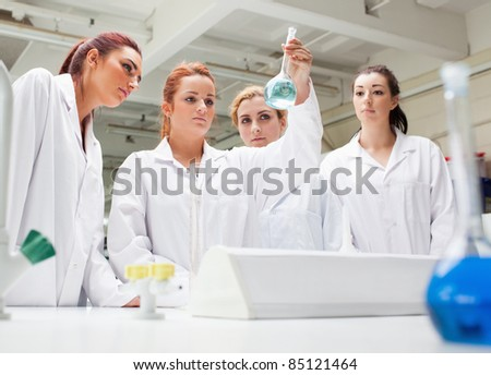 Chemistry students looking at a liquid in a laboratory - stock photo