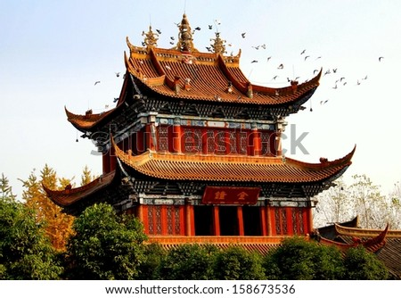 Chengdu, China:  A flock of doves circles the ornate bell tower with its flying eaved roofs at the Zhao Jue Buddhist Temple  - stock photo