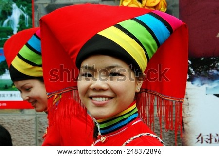 Chengdu, China - April 12, 2006:  Smiling Chinese woman wearing traditional Yi People clothing  with large headdress on historic Jin Li Street - stock photo