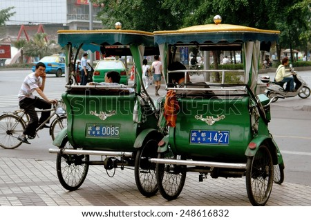 Chengdu, China - May 7, 2008:  Two pedicab taxis parked on busy Jong Fu Road waiting for fares - stock photo