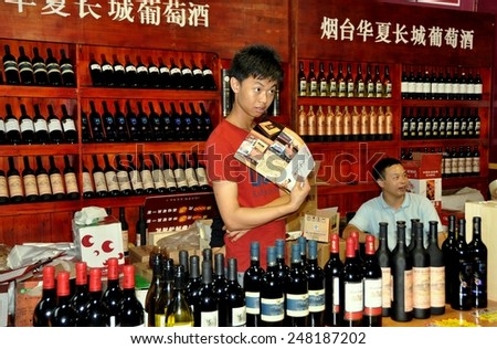 Chengdu, China - September 15, 2010:  Vendors at their booth selling local Chinese and European wines at the 10th Chinese Moon Cake Festival at the annual Sichuan and Tianfu Food Fair - stock photo