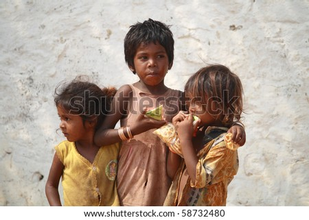 CHENNAI, INDIA - MAR 15: Poor Indian beggar girls on street  eating a piece of watermelon on March  15, 2009 in Chennai, India. Children of the early ages are often brought to the begging profession. - stock photo