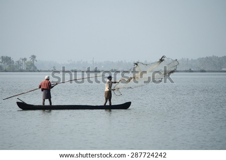 CHERAI, INDIA - MAY 10 : Unidentified fishermen in a boat catch fish by throwing net in to the backwaters in a misty morning on May 10, 2011 in Cherai,Kerala, India. - stock photo