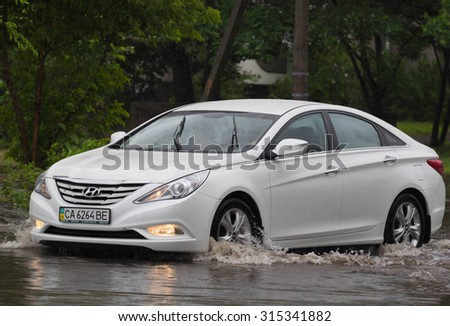 CHERKASSY, UKRAINE- JUNE 27, 2015: cars driving on a flooded road during a flood caused by heavy rain, in Cherkassy.
