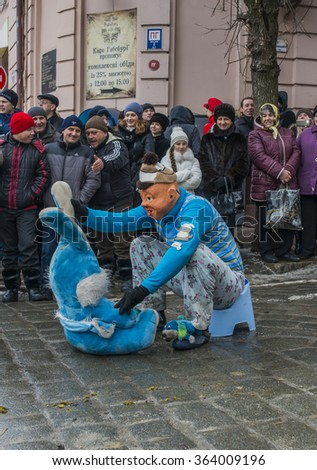 CHERNIVTSI, UKRAINE - JAN 15, 2015: Malanka Festival in Chernivtsi. Folk festivities on the streets dressed people in historical costumes. Malanka dressed child on the pot.