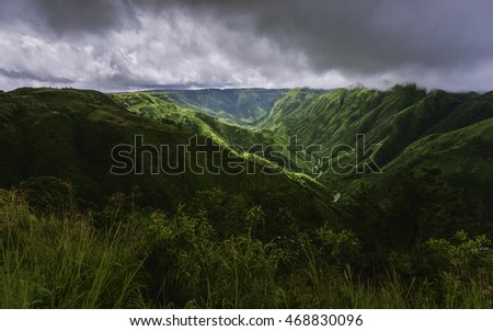 Cherrapunji, Meghalaya, India. Storm clouds over the Khasi Hills as streaks of light break through the clouds to highlight the impressive contours of the mountains near Cherrapunjee, Meghalaya, India.