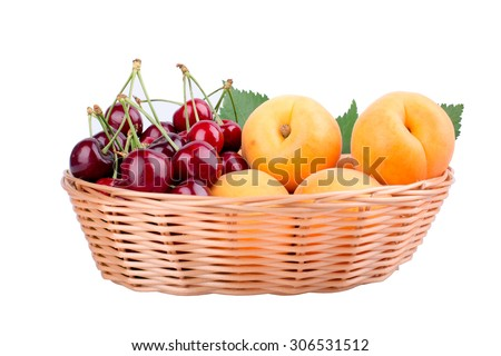 Cherries and apricots in the wooden basket isolated on white