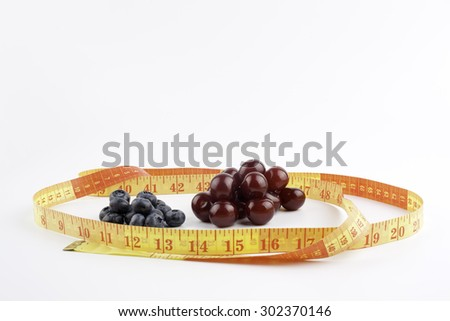 Cherries, blueberries and tape measure on a white background. - stock photo