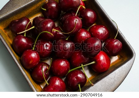 Cherries in a rustic ceramic bowl on a kitchen table