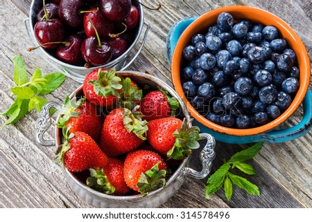 Cherries in an iron bucket, blueberries in a blue vintage bowl, strawberries in a silver bowl and mint leaves on an old wooden table. Top view.