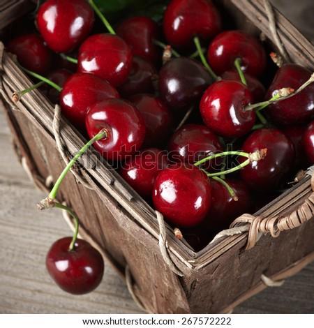 Cherries in basket on vintage wooden background. - stock photo