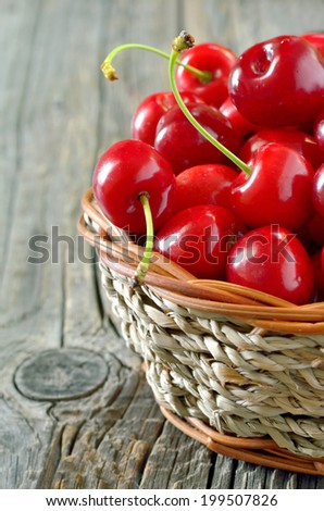 cherries in straw basket isolated on old wooden background