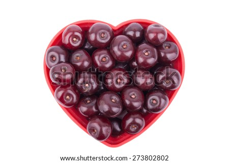 Cherries on a plate in the shape of a heart on a white background. - stock photo