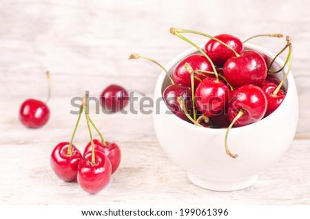 cherries on a white wood background. toning. selective focus on cherries in the bowl