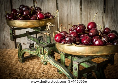 cherries with green kitchen scales and cut wood