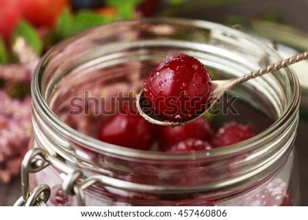 Cherries with sugar in big glass jar - stock photo