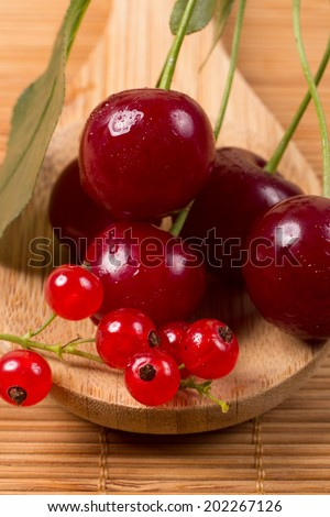 Cherry and currant on wooden spoon close up