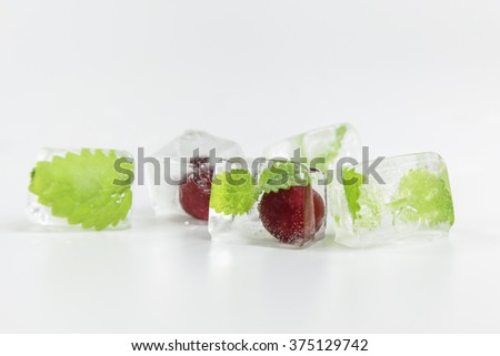 cherry and mint leaf frozen in ice cubes on white background - stock photo