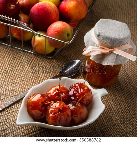 Cherry apples covered in syrup on white saucer, spoon, jar of homemade marmalade jam and apples in metal wire basket on burlap, square. Apple fruit confiture jam marmalade. - stock photo
