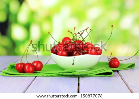 Cherry berries in bowl on wooden table on bright background - stock photo
