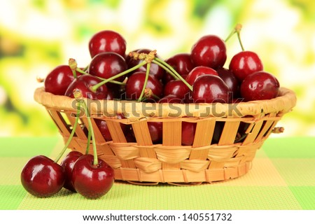 Cherry berries in wicker basket on table on bright background