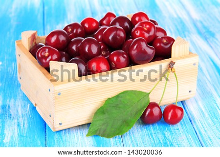 Cherry berries in wooden box on wooden table close-up