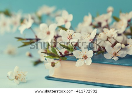 Cherry blossoms and old book on turquoise background, beautiful spring flower, vintage card, selective focus