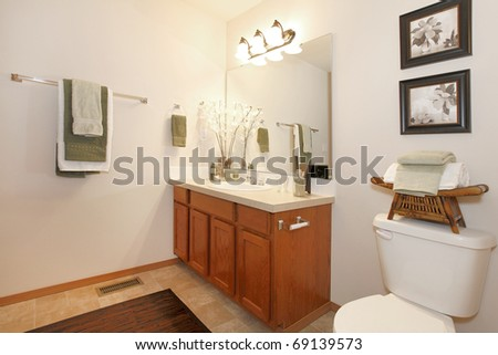 Cherry cabinet and yellow curtains in bathroom with art. - stock photo