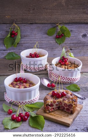 Cherry Clafoutis, traditional French dessert. Baked batter pudding with cherries, sprinkled with icing sugar and decorated with fresh cherries. - stock photo