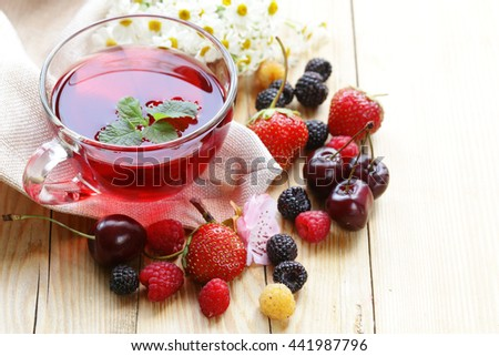 cherry fruit tea in a glass cup and fresh berries