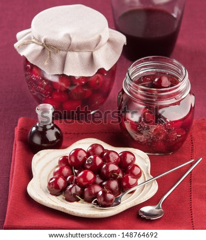 cherry in juice in the pot on a red napkin - stock photo