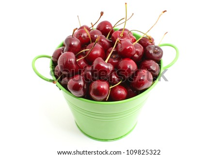 Cherry in the green tin bucket isolated on white