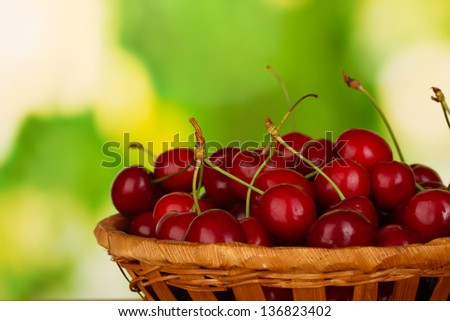 cherry in wicker bowl on wooden table on green background close-up