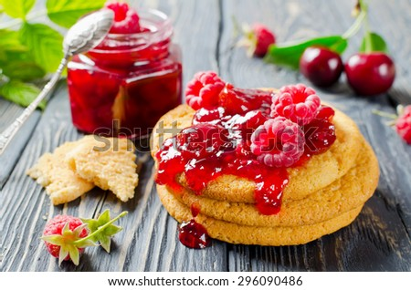 Cherry jam and raspberry in glass jars on wooden table - stock photo