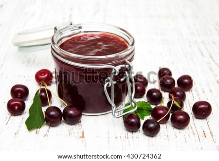 Cherry jam with fresh berries on a wooden background - stock photo