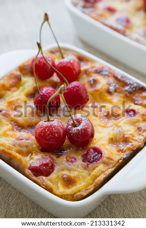 Cherry mini pies in the ceramic baking mould on the linen cloth.Close up - stock photo