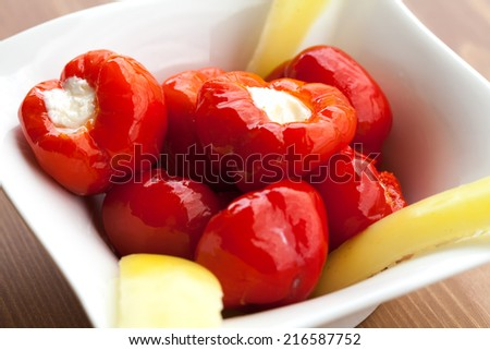 Cherry peppers stuffed with creamy cheese in olive oil. - stock photo