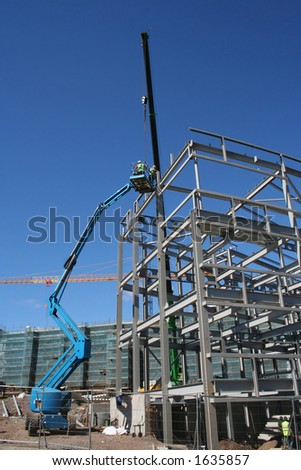 Cherry picker and crane beside metal frame of new building - stock photo