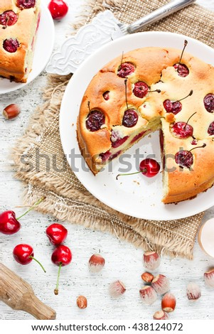 Cherry pie - delicious cake with cherry and nuts on white kitchen table with ingredients top view - stock photo