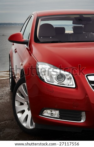 Cherry red car front bumper, light and wheel detail - stock photo