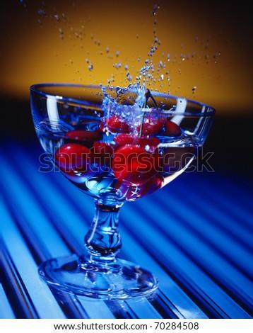 cherry splashes into a glass - stock photo