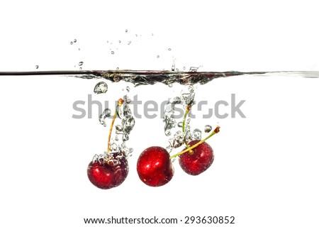 Cherry splashing into water on white background - stock photo