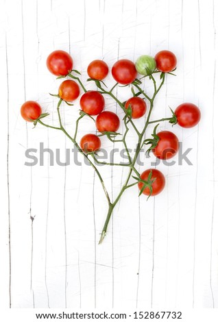 Cherry tomato branch on the old cracked background - stock photo