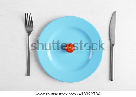 Cherry tomato in a blue plate on white table. Top view. - stock photo