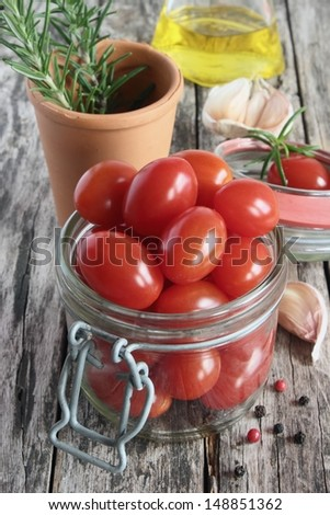 Cherry tomato in the glass and rosemary on the wooden background