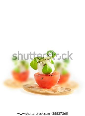 Cherry tomato, mozzarella chess and basil leaf on cracker isolated on white - stock photo