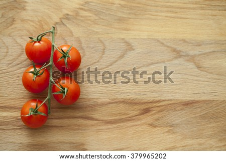 cherry tomato on a wooden surface empty for text; a bunch of tomatoes on wooden background